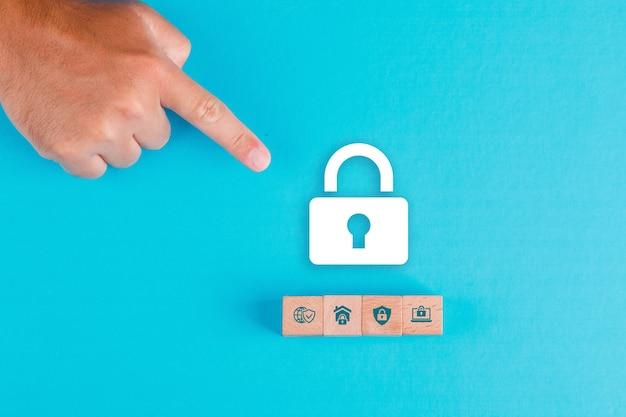 Sicherheitskonzept mit holzklötzen, papierschlosssymbol auf blauem tisch flach legen. mann hand zeigt. Kostenlose Fotos