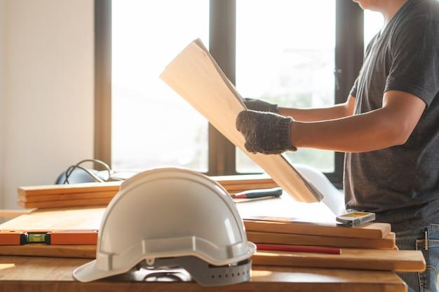 Sicherheitsschutzhelm auf dem tisch und arbeitskraft als hintergrund. Premium Fotos