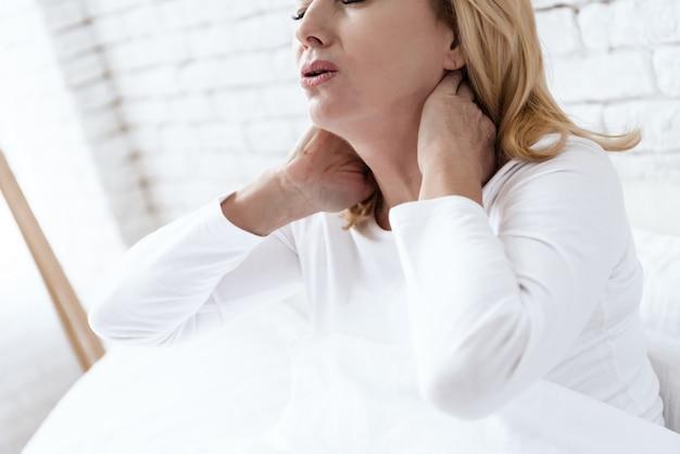 Sie hält die hände an den hals an der weißen wand. Premium Fotos