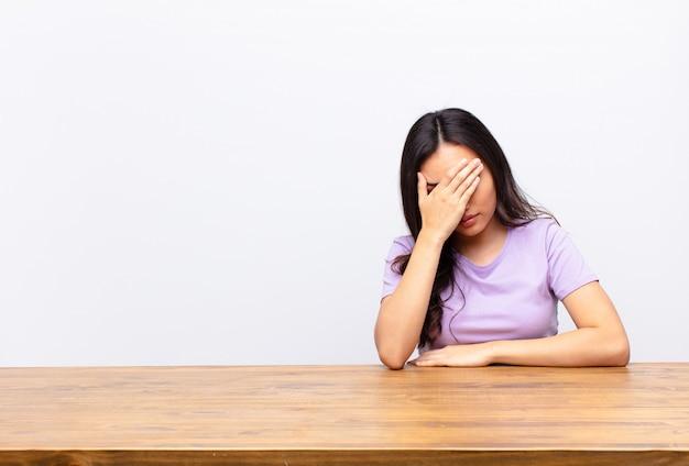 Sie sehen gestresst, beschämt oder verärgert aus, haben kopfschmerzen und bedecken das gesicht mit der hand Premium Fotos