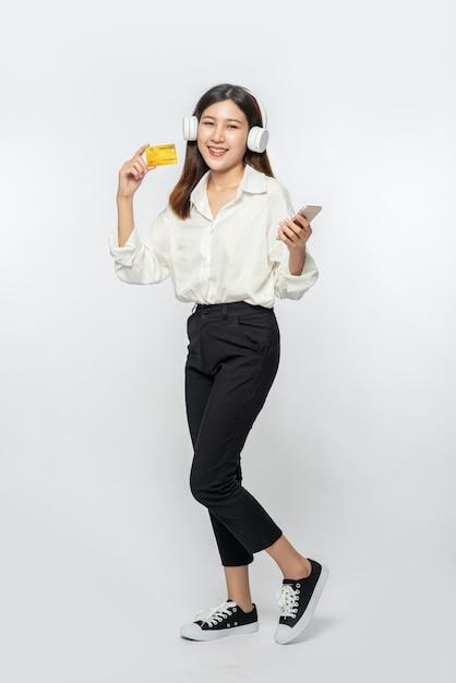 Sie trug ein weißes hemd und eine dunkle hose, um einkaufen zu gehen und eine kreditkarte und ein smartphone in der hand zu halten Kostenlose Fotos