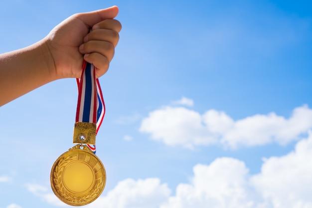 Siegerhand hob das halten von goldmedaillen mit thailändischem band gegen blauen himmel an. Premium Fotos