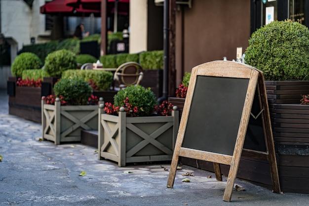 Signboard stand blackboard cafe menu shop restaurant mit büschen in töpfen im freien Kostenlose Fotos