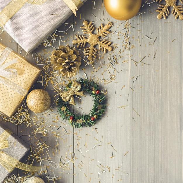 Silber- und goldgeschenkboxen und weihnachten, die einzelteile auf hölzernem hintergrund verzieren Premium Fotos