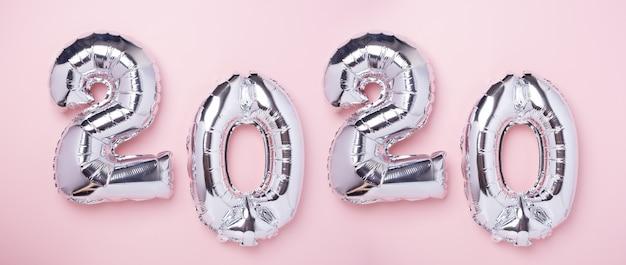 Silberne ballone in form von nr. 2020 auf rosa Premium Fotos
