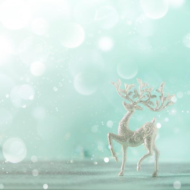 Silberne funkeln weihnachtsrotwild auf blauem hintergrund mit lichtern bokeh, kopienraum. Premium Fotos