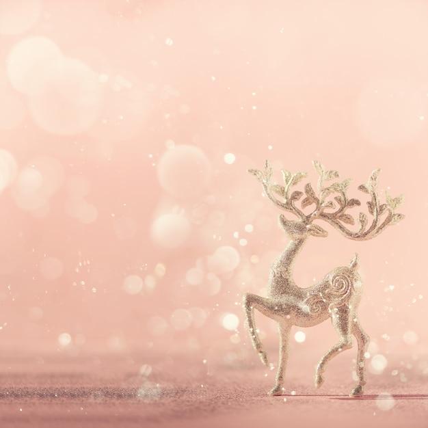 Silberne funkeln weihnachtsrotwild auf rosa hintergrund mit lichtern bokeh, kopienraum. Premium Fotos