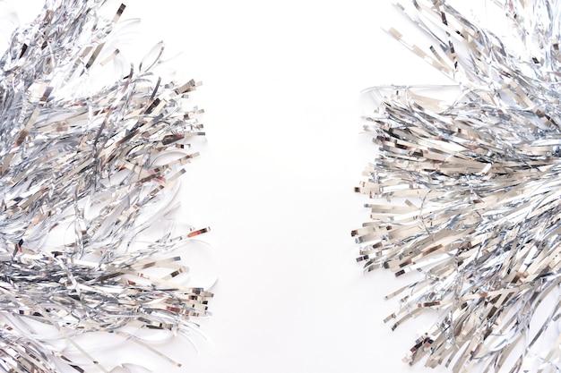 Silberne metallfolienlamettastreifen lokalisiert auf weißem hintergrund, weihnachten oder festlicher dekorationsgirlande. Premium Fotos