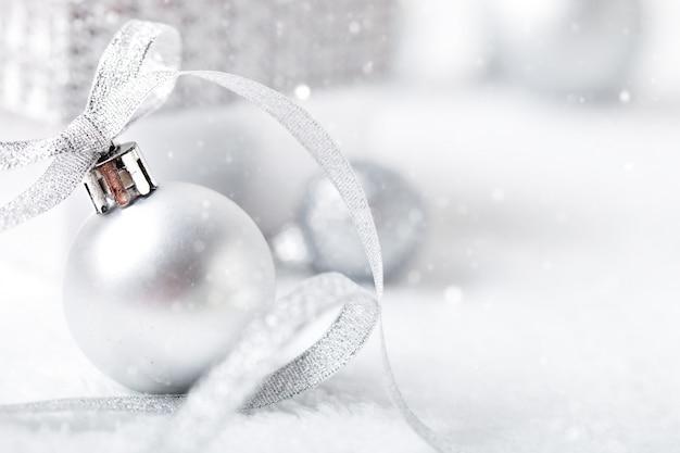 Silberne weihnachtsspielwaren auf einem hellen hintergrund. Premium Fotos