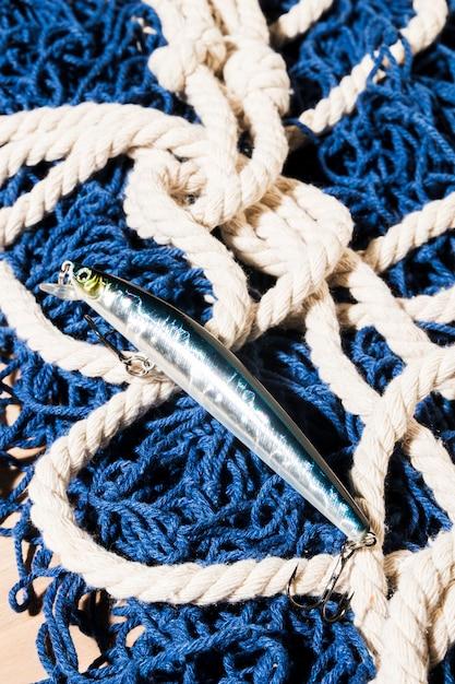 Silberner fischköder auf blauem fischernetz Kostenlose Fotos