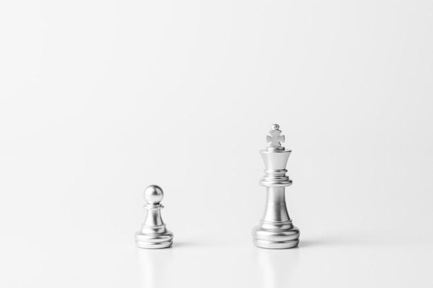 Silberner könig und bauernschach stehen auf dem weißen schreibtisch. Premium Fotos