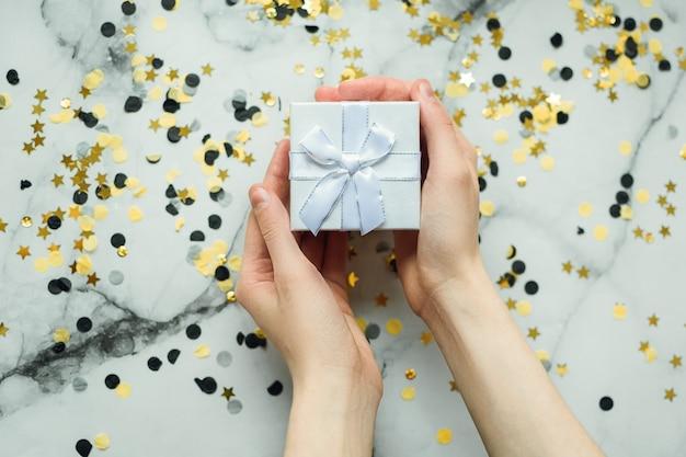 Silbernes geschenk in den händen eines mädchens ohne maniküre Premium Fotos