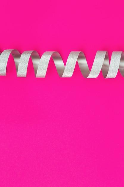 Silbernes gewundenes band auf rosa papier. Premium Fotos