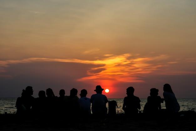 Silhouette alle menschen im familientreffen blick sonnenuntergang himmel am strand Premium Fotos
