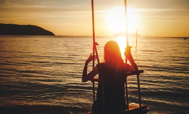 Silhouette einer frau auf einer schaukel bei sonnenuntergang am meer, meditation naturbeobachtungsurlaub und solo-reisekonzept Premium Fotos