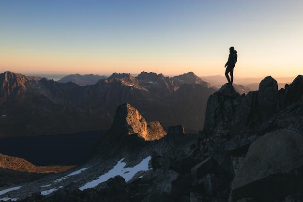 Silhouette einer person, die auf der spitze eines hügels unter dem schönen bunten himmel am morgen steht Kostenlose Fotos