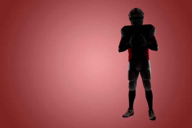 Silhouette eines fußballspielers mit einer roten uniform an einer roten wand Premium Fotos