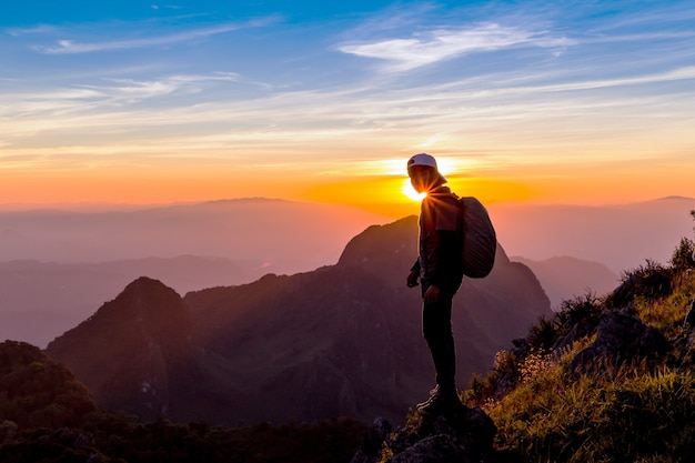 Silhouette eines mannes auf einem berggipfel. personenschattenbild auf dem felsen. Premium Fotos