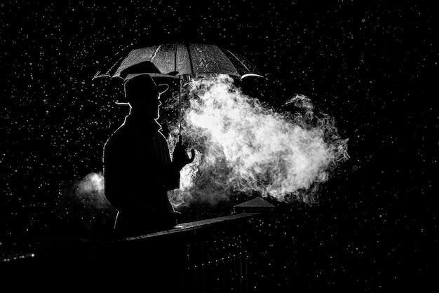 Silhouette eines mannes in einem hut unter einem regenschirm in der nacht im regen in der stadt im alten verbrechen noir-stil Premium Fotos