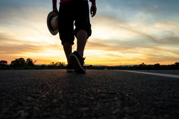 Silhouette eines mannes zu fuß auf der autobahn zum zeitpunkt des sonnenuntergangs Premium Fotos