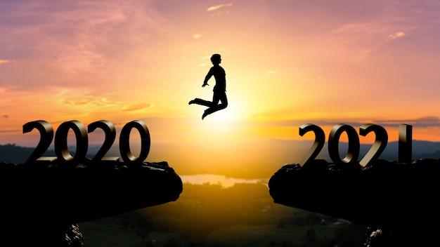 Silhouette mann springen zwischen 2020 und 2021 jahren mit sonnenuntergang wand, jahr 2021 konzept Premium Fotos