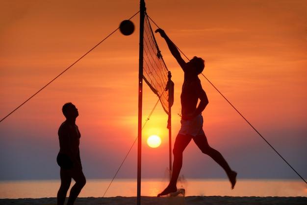 Silhouette spielen beachvolleyball. sonnenuntergang zeit Premium Fotos