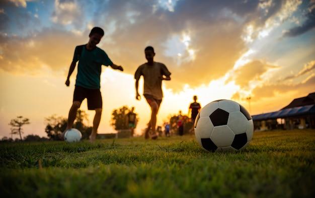 Silhouettieren sie aktionssport draußen einer gruppe kinder, die den spaß haben, fußballfußball für übung zu spielen Premium Fotos