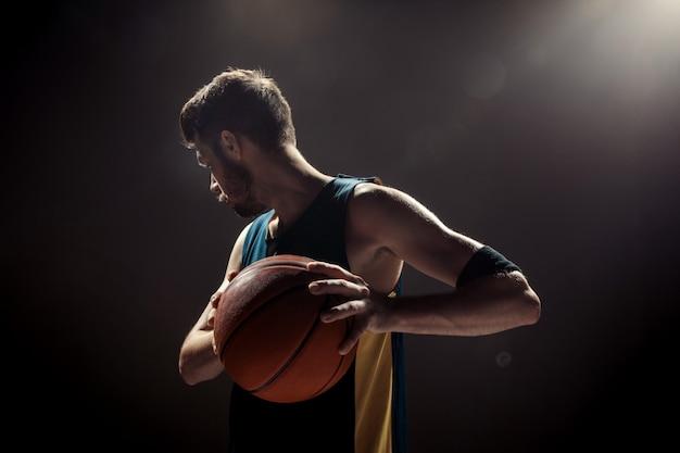 Silhouettieren sie ansicht eines basketball-spielers, der korbball auf schwarzer wand hält Kostenlose Fotos