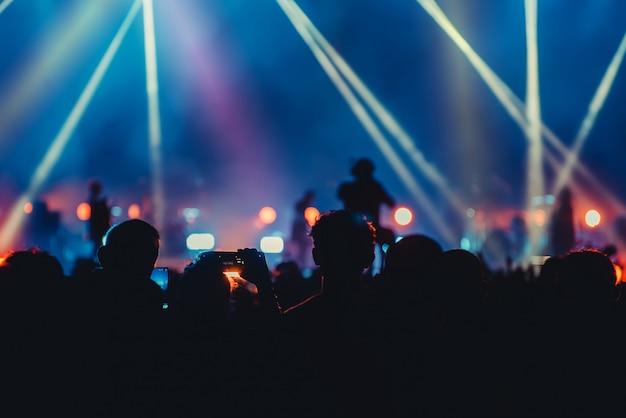 Silhouettieren sie bild und defocused der bunten beleuchtung des unterhaltungskonzerts auf stadium Premium Fotos