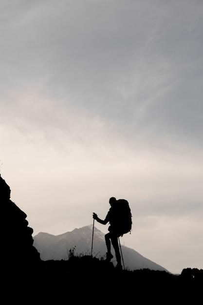 Silhouettieren sie das dünne mädchen, das auf dem felsen mit dem wandern des rucksacks und der spazierstöcke steht Premium Fotos