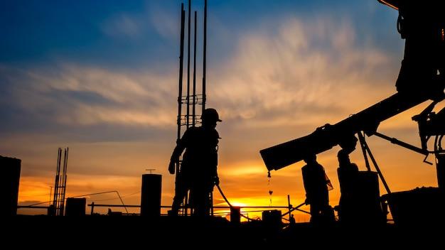 Silhouettieren sie den bauarbeiter beton, der während der betonierbetonungsböden des gebäudes in der baustelle gießt Premium Fotos