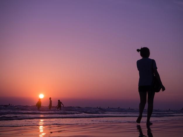Silhouettieren sie den schatten der jungen asiatischen frau, die auf strand mit sonnenuntergang geht. konzept des urlaubsstrandes. Premium Fotos