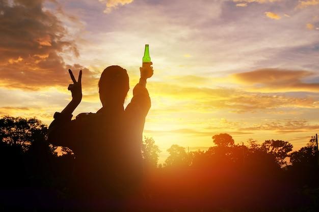 Silhouettieren sie die frau angehobenen hände, die eine grüne bierflasche auf dem sonnenunterganghimmel halten, Premium Fotos