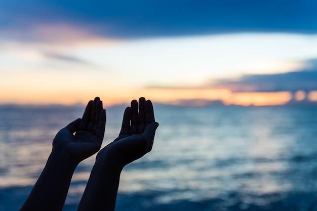 Silhouettieren sie die frauenhände, die vom gott während des sonnenuntergangs, hoffnungskonzept beten. Premium Fotos