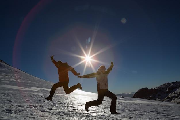 Silhouettieren sie die paare, die auf schnee gegen sonne und blauen himmel springen Premium Fotos