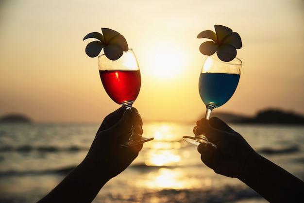 Silhouettieren sie die paarhand, die cocktailglasdekoration mit plumeriablume mit strand hält - glücklich entspannen sie sich feierferien im seenaturkonzept Kostenlose Fotos