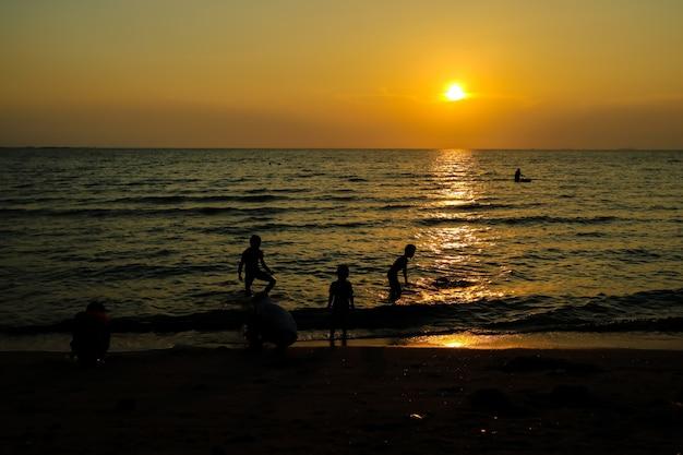 Silhouettieren sie familie und haustier am strand- und seesandsonnenuntergang Premium Fotos