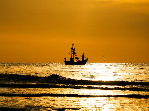 Silhouettieren sie fischer in einem boot auf sonnenuntergangmeer Premium Fotos