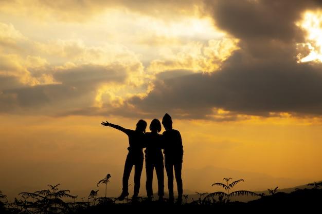 Silhouettieren sie, gruppe des glücklichen mädchens spielend auf hügel, sonnenuntergang Kostenlose Fotos