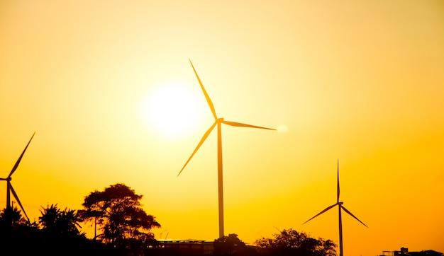 Silhouettieren sie windkraftanlagen auf landfeld mit sonnenunterganghimmel Premium Fotos