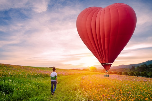 Silhouettiert vom asiatischen mann, der auf kosmos steht, blüht mit rotem heißluftballon in form eines herzens über dem sonnenuntergang. Premium Fotos