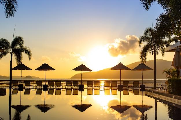 Silhouettiertes bild, der schöne sonnenaufgang am strand mit bett und swimmingpool. Premium Fotos