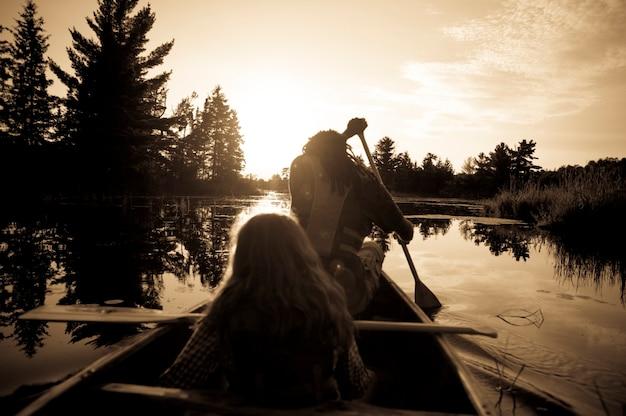 Sillhouette von den leuten, die ein kanu am see des holzes, ontario rudern Premium Fotos