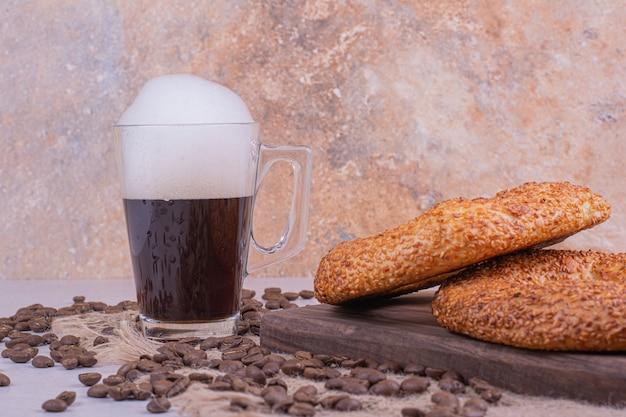 Simit rollt auf holzbrett mit einem glas getränk und kaffeebohnen herum. Kostenlose Fotos