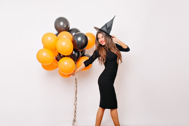 Sinnliche frau im hexenkostüm, das auf halloween wartet und orangefarbene luftballons hält Kostenlose Fotos