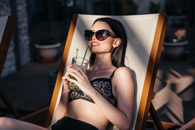Sinnliche frau mit sonnenbrille ein cocktail trinkend Premium Fotos
