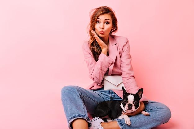 Sinnliche ingwerdame, die auf dem boden mit niedlicher französischer bulldogge sitzt. jocund trendige frau, die mit welpen auf pastell aufwirft. Kostenlose Fotos