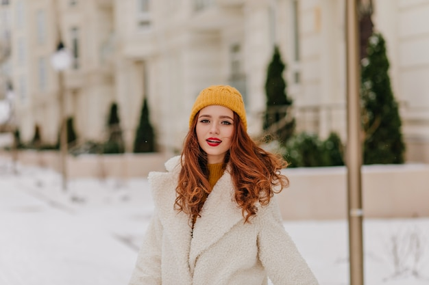 Sinnliche ingwerfrau, die auf unschärfestraße aufwirft. kaukasisches hübsches mädchen, das winter genießt. Kostenlose Fotos