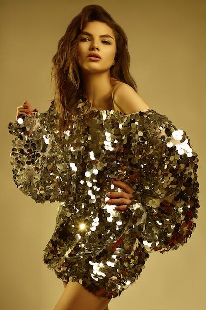 Sinnliche schöne brunettefrau in einem glänzenden modekleid von pailletten Premium Fotos