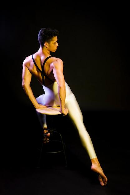 Sinnlicher männlicher balletttänzer, der im scheinwerfer sitzt Kostenlose Fotos